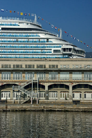 close up of Costa Venezia behind a building of Trieste Cruise Terminal Trieste Costa Crociere Costa Venezia Trieste Cruise Terminal Cruise Terminal Naval Design Cruise Ship Sea Travel No People Waterfront Architecture Built Structure Building Exterior Outdoors Mode Of Transportation Low Angle View Luxury Nautical Vessel Maritime Photography City Water Close-up