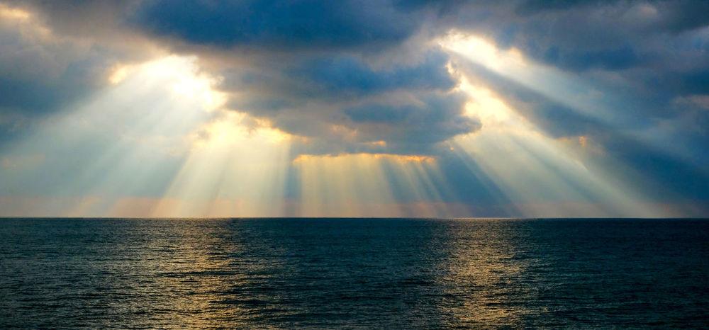 Sun Beams Shining Thru The Clouds Sunlight Through Clouds Water Sky Sea Beauty In Nature Sunbeam Horizon Cloud - Sky Scenics - Nature Horizon Over Water Tranquility Sunlight Idyllic Tranquil Scene Nature No People Reflection Sun Waterfront Outdoors