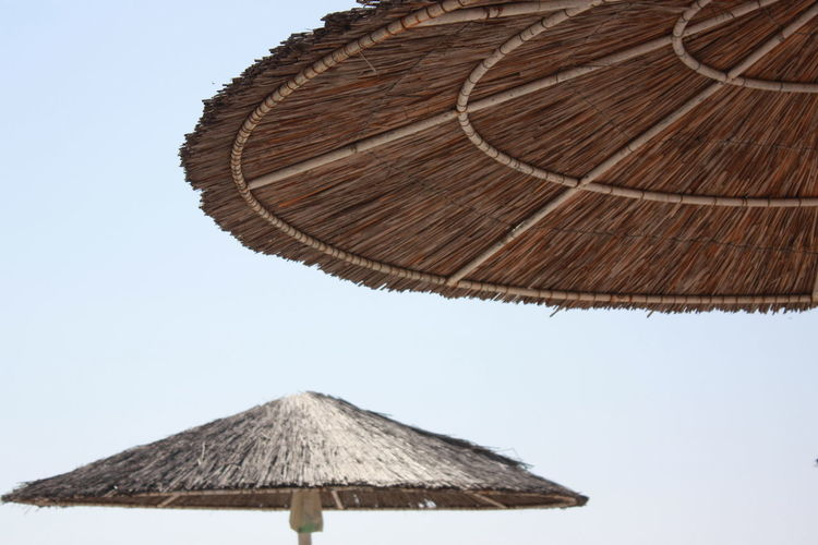 Beach Umbrella Brown Clear Sky Close-up Day Low Angle View Nature No People Outdoors Parasol Protection Roof Security Shade Sky Sunshade Thatched Roof Umbrella Wood - Material Travel Destinations Low Angle View Single Object Sunny Roof Clear Sky Nature Sunlight Moments Of Happiness 2018 In One Photograph