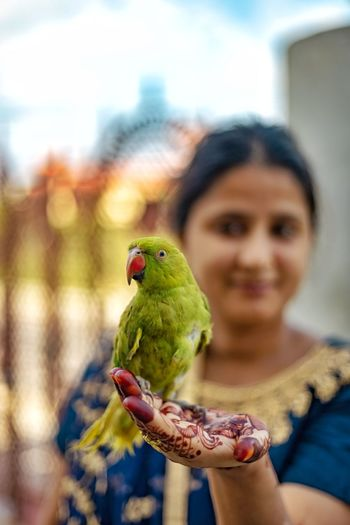 Woman with henna tattoo holding parrot