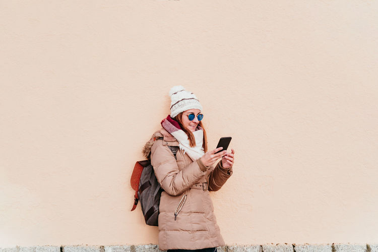 Woman wearing warm clothing using smart phone while standing against wall