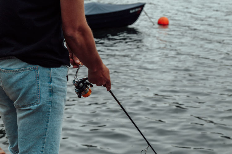 Midsection Of Man Holding Fishing Rod