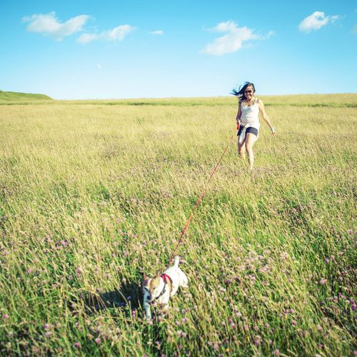 Full length of girl running on grassy field