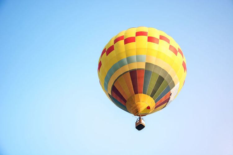 Low Angle View Of Yellow Hot Air Balloon Flying Against Clear Sky