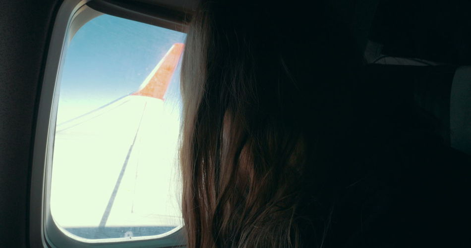 Low angle view of woman looking through airplane window