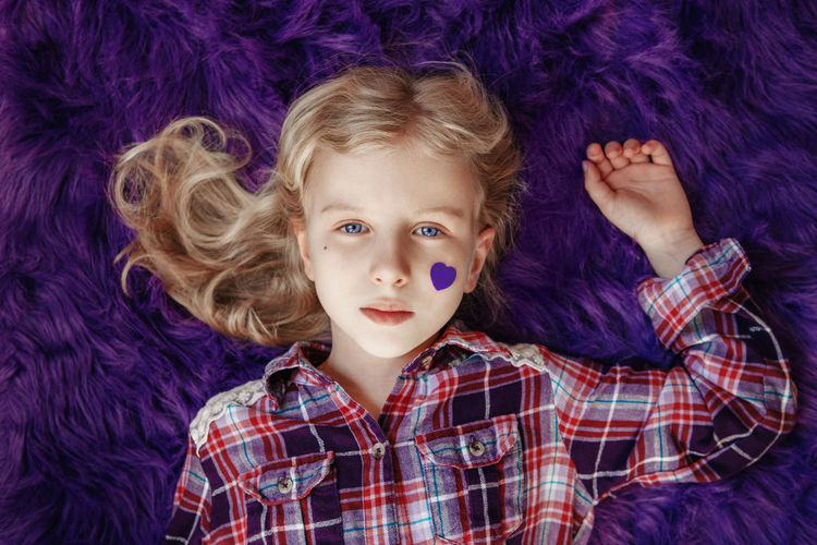 International epilepsy awareness day. cute caucasian girl with small violet purple heart on cheek
