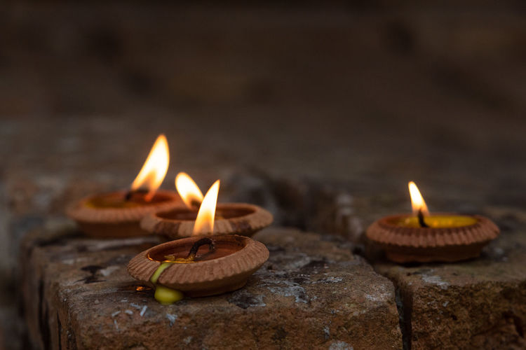 Belief Burning Candle Celebration Close-up Electric Lamp Fire Fire - Natural Phenomenon Flame Focus On Foreground Glowing Heat - Temperature Illuminated Lighting Equipment Nature No People Oil Lamp Religion Selective Focus Spirituality