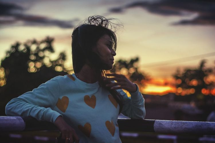 Young woman leaning on railing against sky during sunset