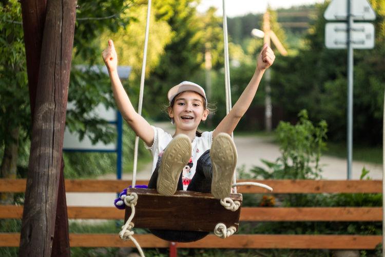 Full length portrait of happy girl enjoying on swing at park