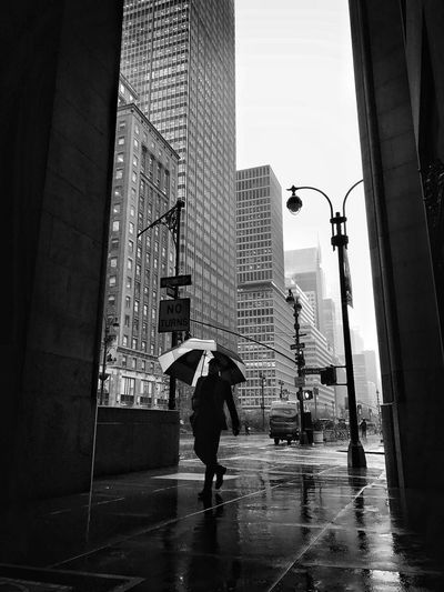 Full length of man with umbrella while walking on sidewalk during rainy season