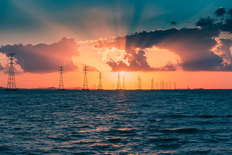 Electricity pylons by sea against sky during sunset