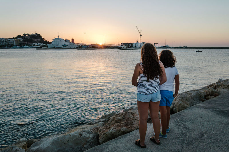 Rear view of siblings looking at sunset over sea