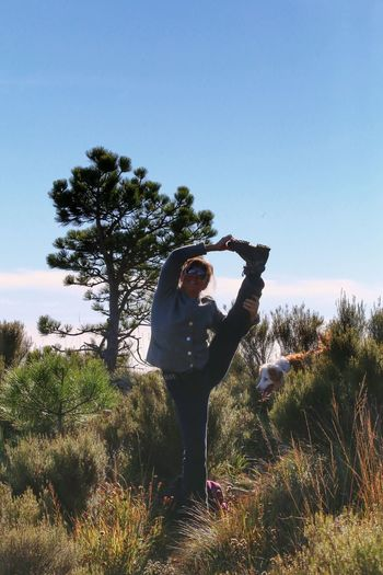 Full length portrait of woman standing on one leg at field against clear sky