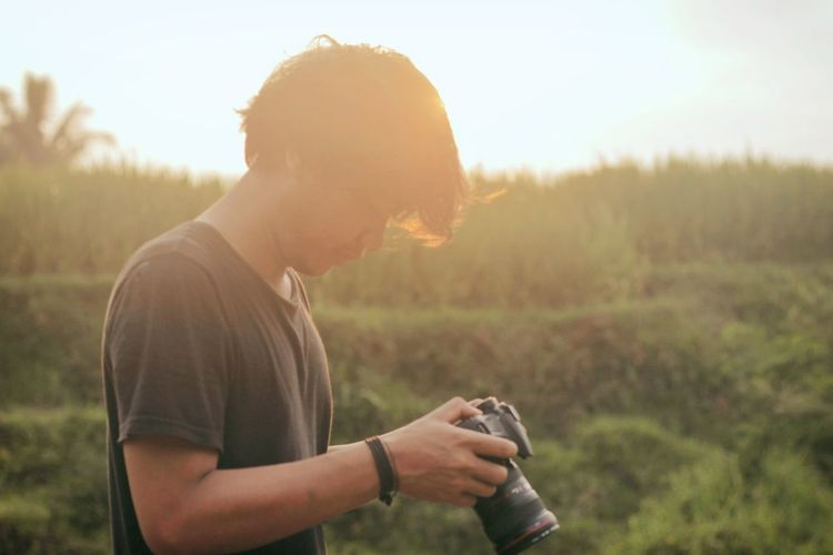Young man using camera on field