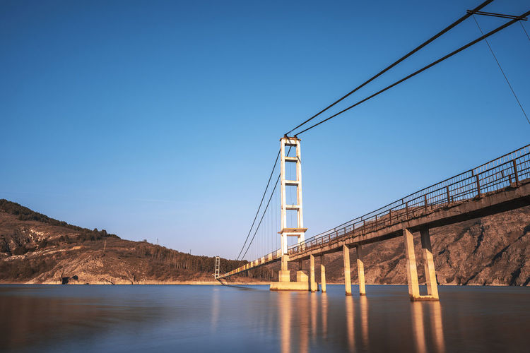 The longest suspension bridge in Bulgaria over Studen Kladenez dam with distance between the two towers of 260m. The only way to reach Lisicite village Reflection Water Sunset Nature Sky Bridge Travel Tower Lake Mountain Direction Pylon Way Suspension Dam Bulgaria Metal Overcast Wooden Suspension Bridge Longest Warm Clothing Clear Sky Connection Bridge - Man Made Structure Blue Built Structure Architecture Transportation No People River Day Waterfront Copy Space Outdoors Bay