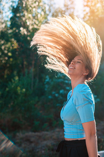 Beautiful woman tossing hair against tree