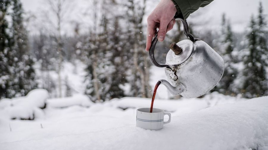 Cropped hand of person pouring tea in cup on snow