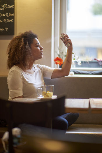 Young woman spraying perfume while sitting in restaurant