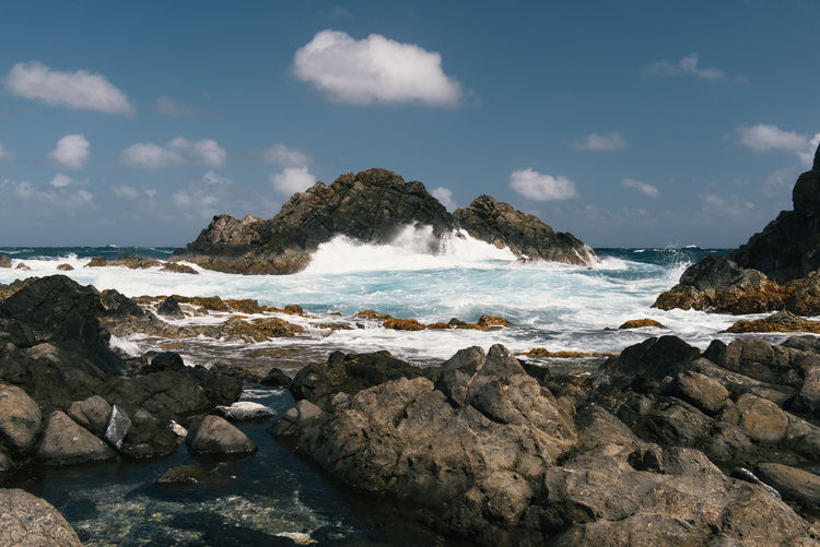 Scenic view of rocky beach against sky