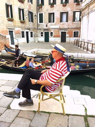 Side view of gondolier sitting on chair by canal in city