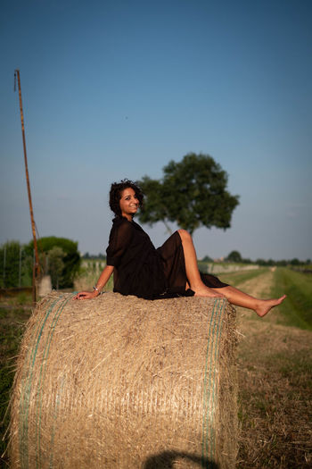 Full length of woman sitting on haystack on field