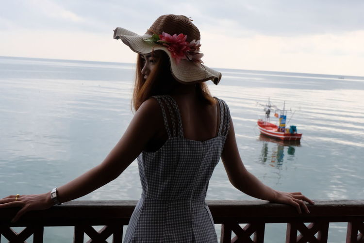 Woman looking away against sea and sky