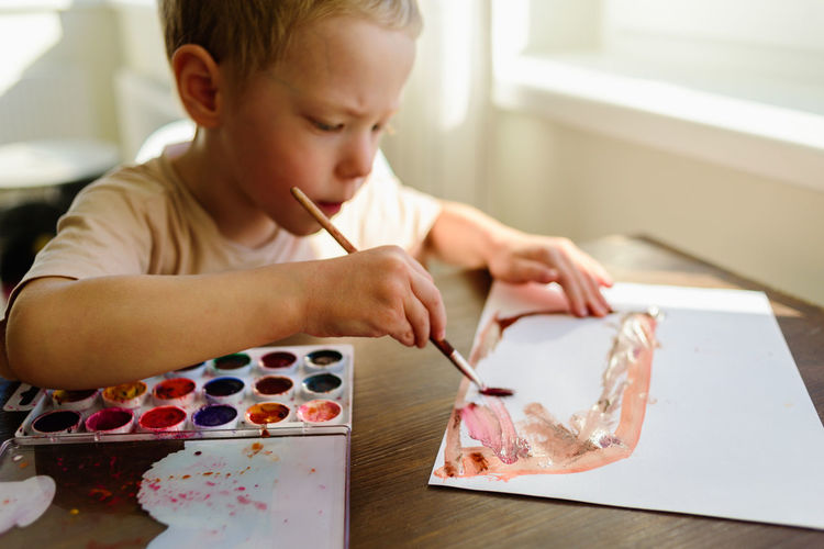 Close-up of boy painting on paper