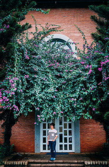 Woman Standing On Porch Amidst Trees Against Door