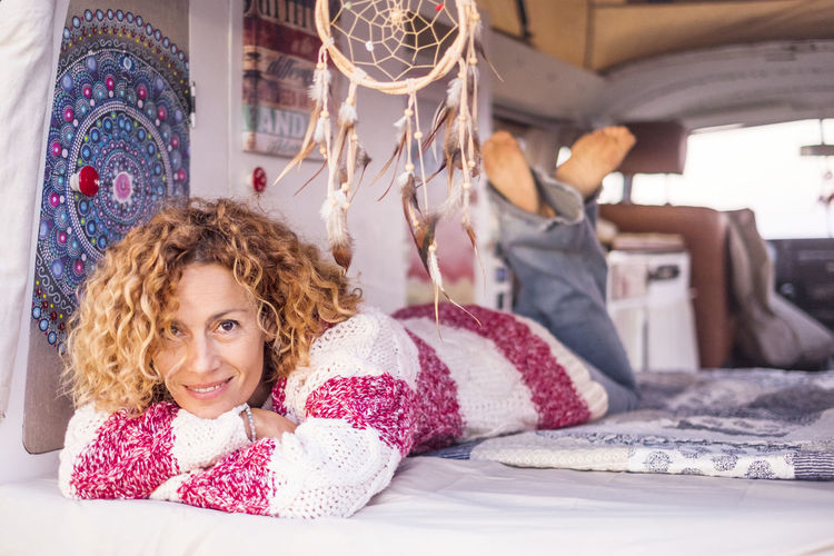 Portrait Of Smiling Mature Woman Lying On Bed In Motor Home