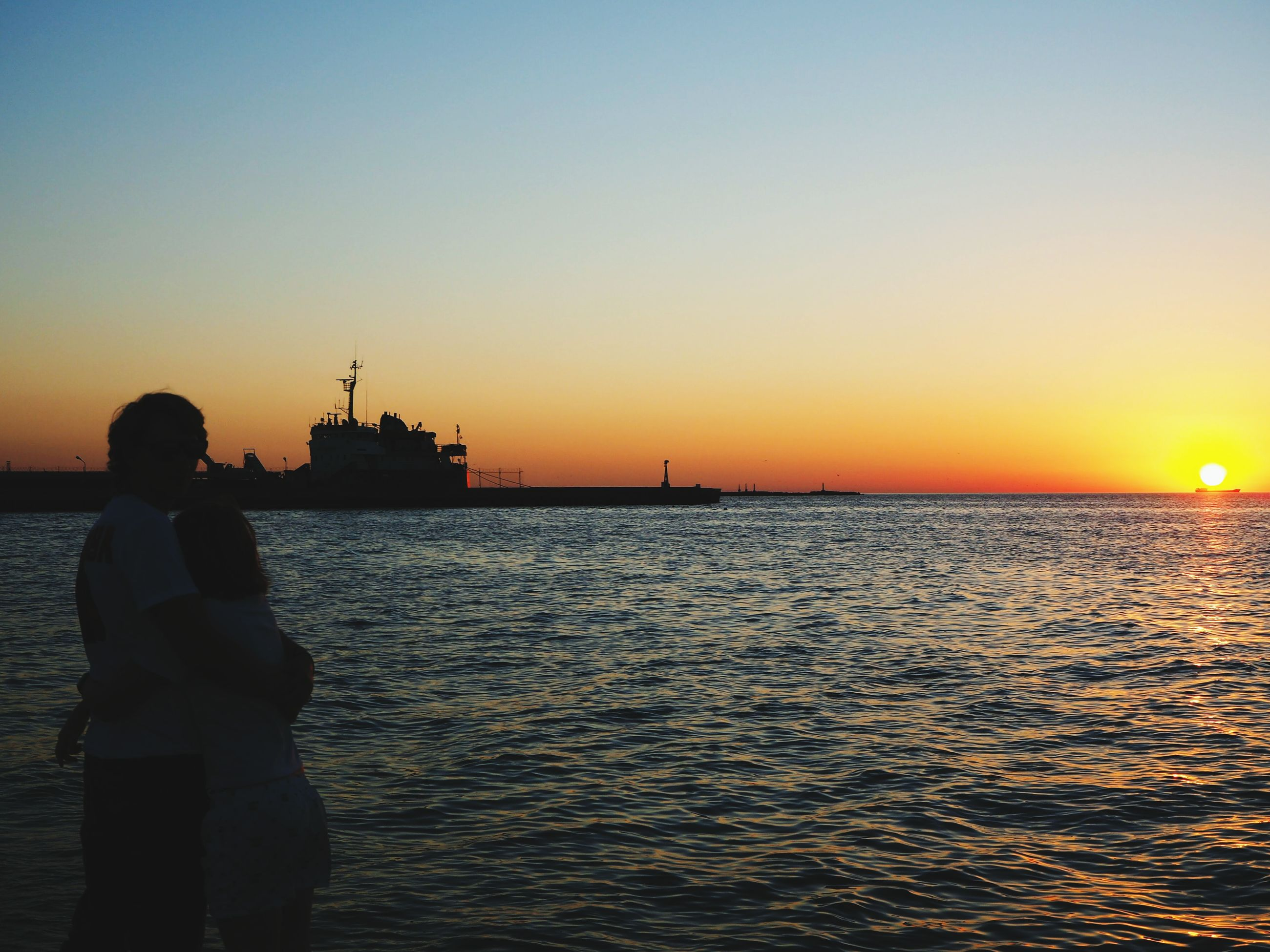 clear sky, sea, sunset, water, standing, silhouette, one person, horizon over water, real people, rippled, outdoors, beauty in nature, nature, sky, day, people, adult