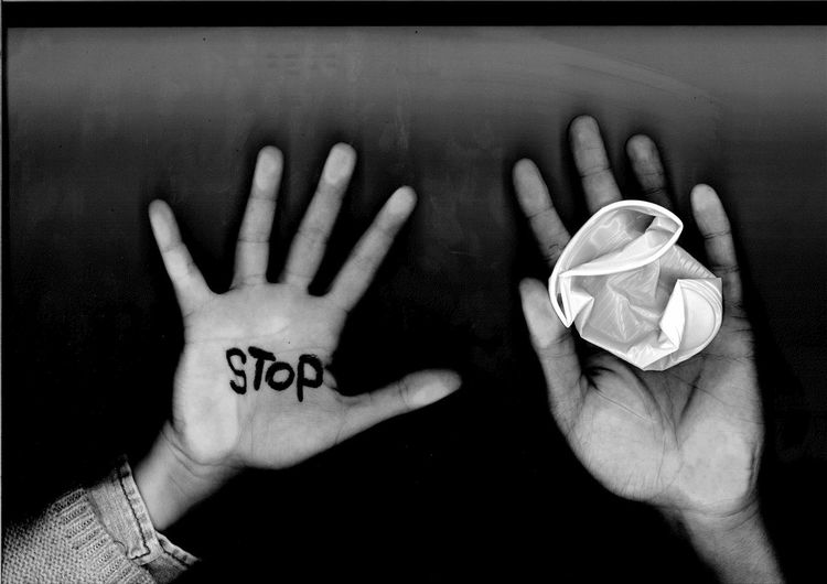 Cropped hands with stop text and crushed plastic cup