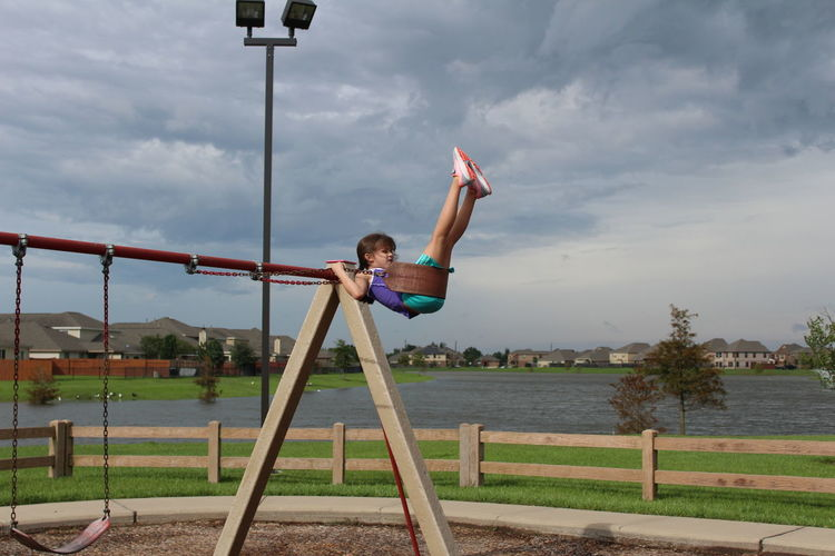 Trying to swing over the swingset. Playground Equipment Swinging Swingset Childhood Cloud - Sky Day Full Length Happiness Lake Lake View Leisure Activity One Person Outdoors Park - Man Made Space People Playground Playing Real People Sky Swing Tree