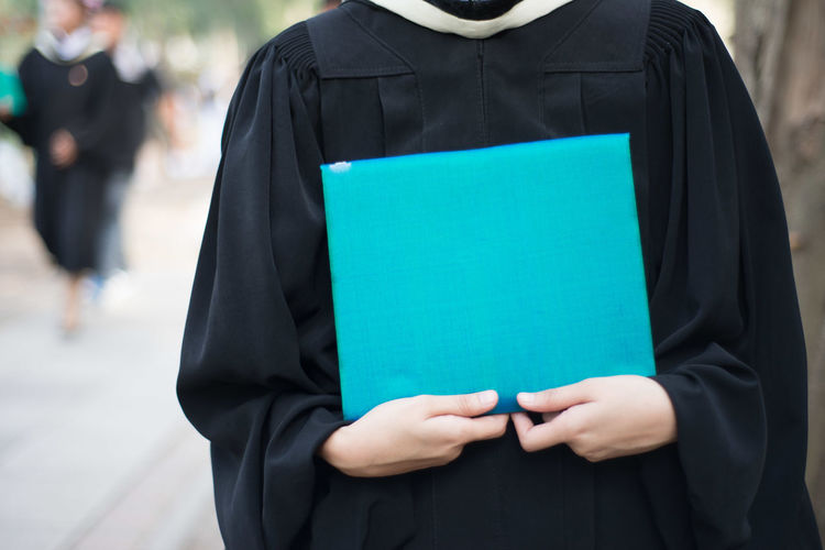 Midsection of woman wearing graduation gown holding document