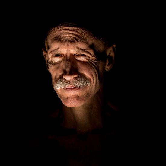 Portrait Of Mature Man Making Face Against Black Background