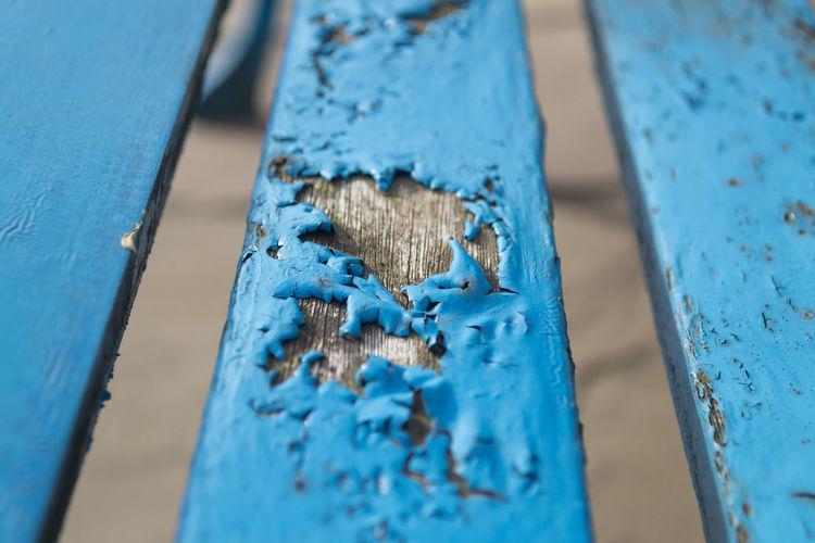 Wooden bench panel with blue paint flaking due to being weathered Bad Condition Blue Built Structure Close-up Damaged Day Decline Deterioration Metal No People Old Outdoors Pattern Peeling Off Run-down Rusty Selective Focus Textured  Weathered Wood - Material