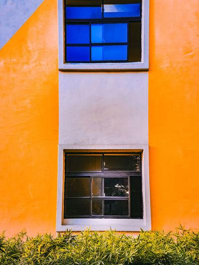 Low angle view of yellow window on orange building