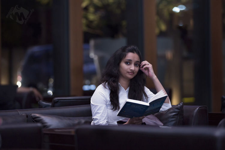 Portrait of young woman reading book in lobby