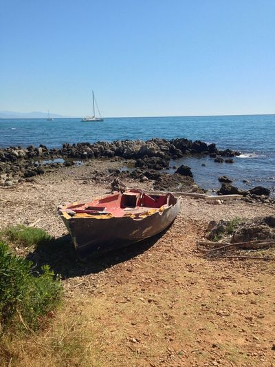 Boat at sea shore against clear sky