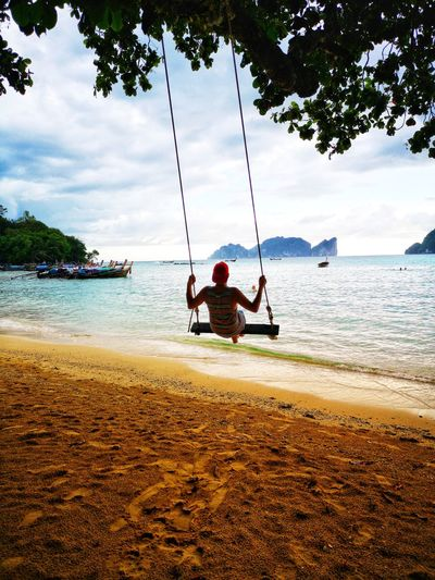 Rear view of man on swing at beach