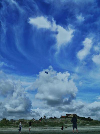 Flying kite on beach against blue sky
