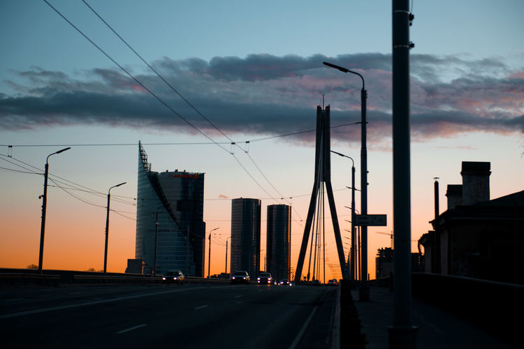 Cityscape Architecture Bridge Bridge - Man Made Structure Building Exterior Built Structure Cable Car City Cloud - Sky Electricity  Europe Mode Of Transportation Office Building Exterior Orange Color Riga Latvia Road Silhouette Sky Skyscraper Street Sunset Transportation Vansubridge Vanšu Tilts