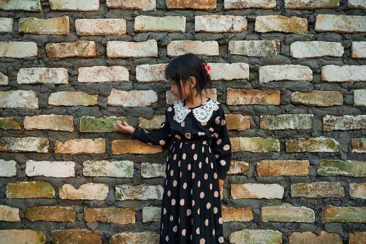Girl standing against brick wall