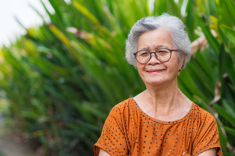 Portrait of an elderly woman arms crossed and smiling while standing in a garden.