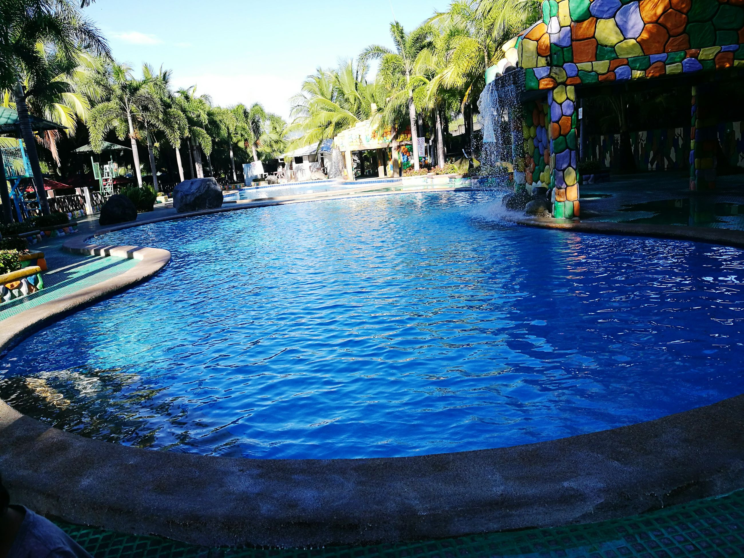 water, swimming pool, tree, blue, outdoors, leisure activity, water park, day, summer, real people, sky, nature, water slide