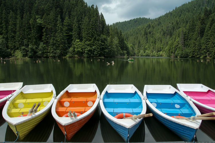 Colorful boats staying on the lake and moutains and forest behind bicaz lake