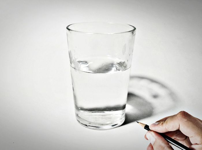 Person holding pencil by glass of drinking water