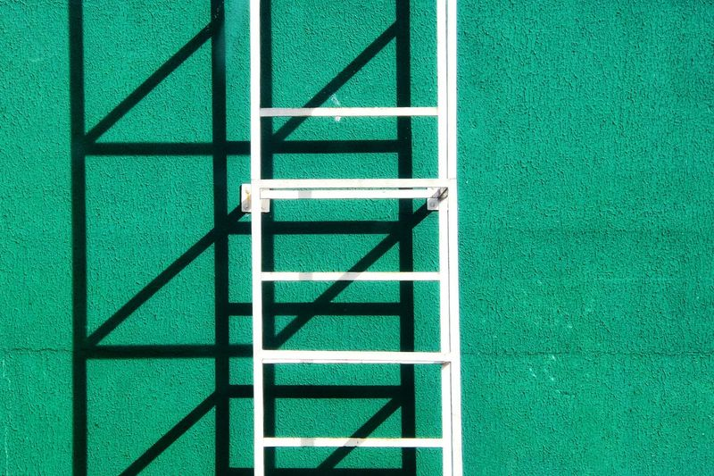 Close-Up Of Metal Ladder Against Green Stucco Wall