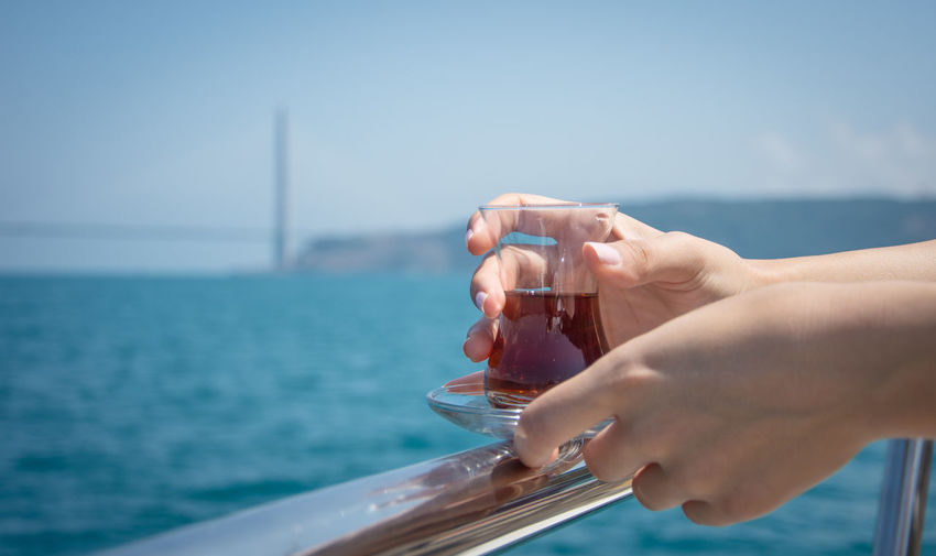 Tea Beauty In Nature Bosphorus Clear Sky Close-up Drink Holding Horizon Over Water Human Body Part Human Hand Leisure Activity Nature Nautical Vessel One Person Outdoors Real People Sailing Scenics Sea Sky Summer Transportation Turkish Tea Vacations Water