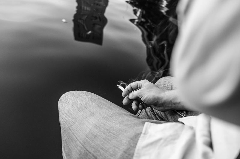 Midsection Of Man Holding Burning Cigarette By Lake