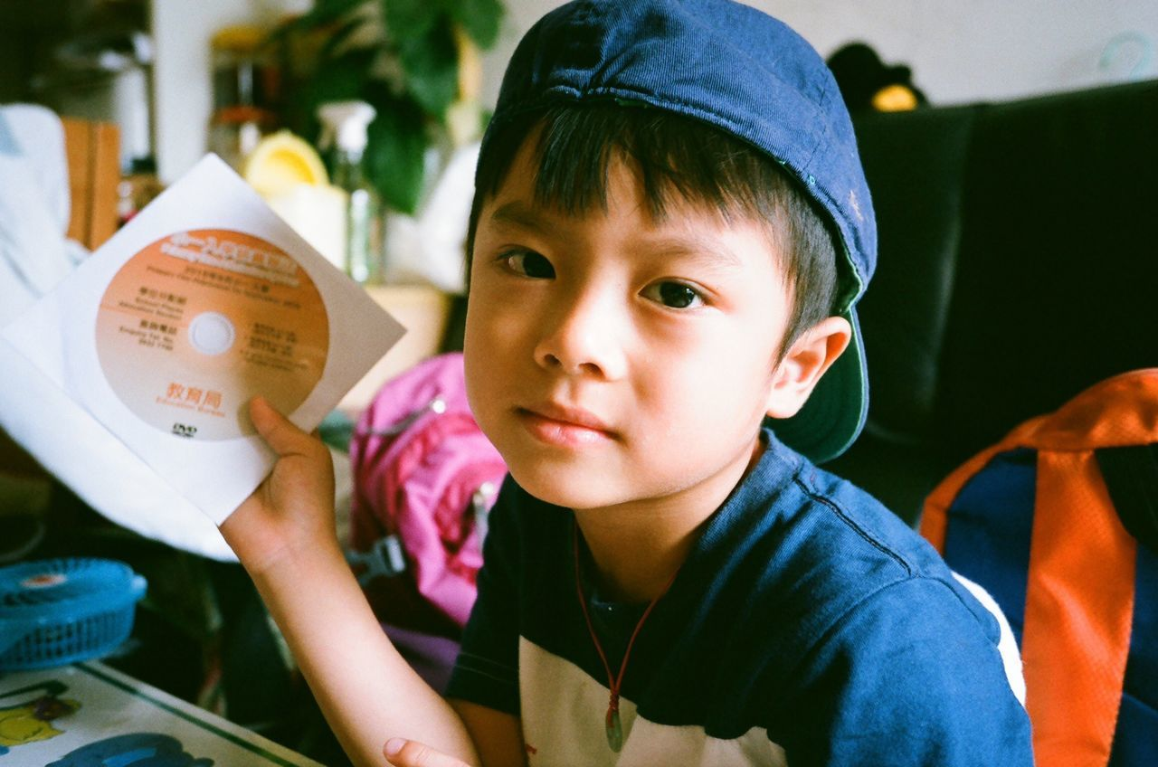 Portrait Of Boy With Compact Disc At Home